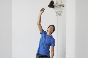 19076056 - man dusting crystal chandelier in home