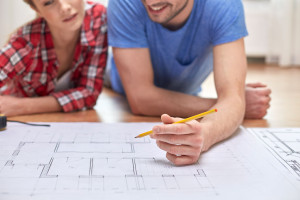 38817493 - repair, building, renovation and people concept - close up of happy couple looking at blueprint at home