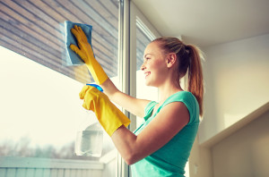 51129854 - people, housework and housekeeping concept - happy woman in gloves cleaning window with rag and cleanser spray at home